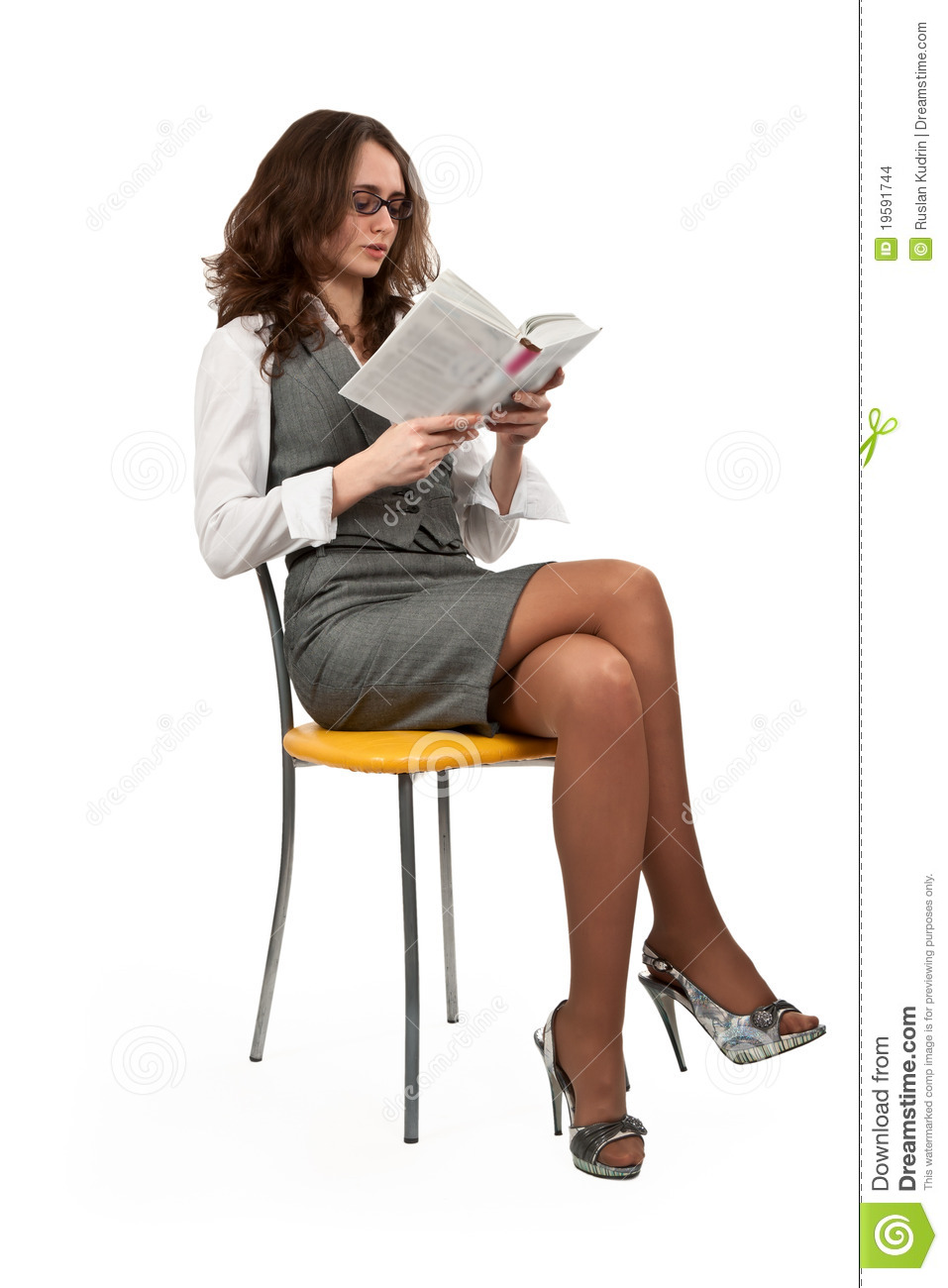 Girl Is Sitting On A Chair And Reading A Book Stock Photo