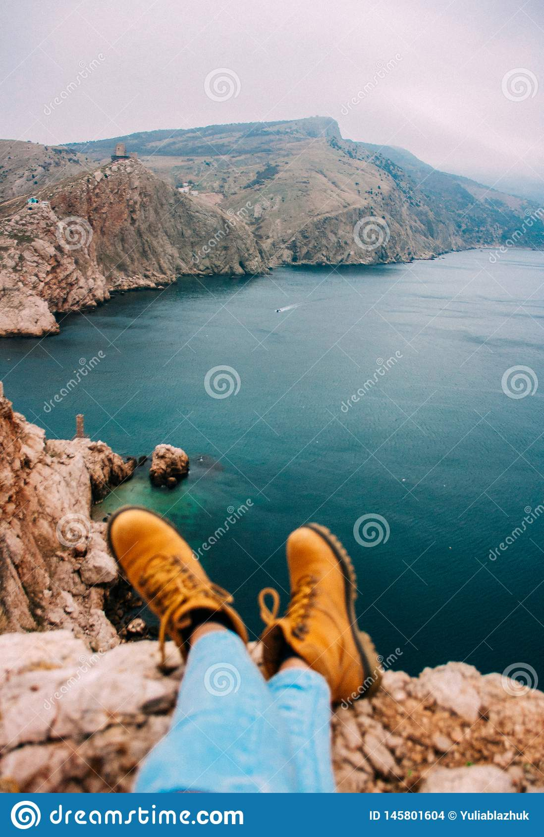 Girl sitting on cliff in front of breakage above sea