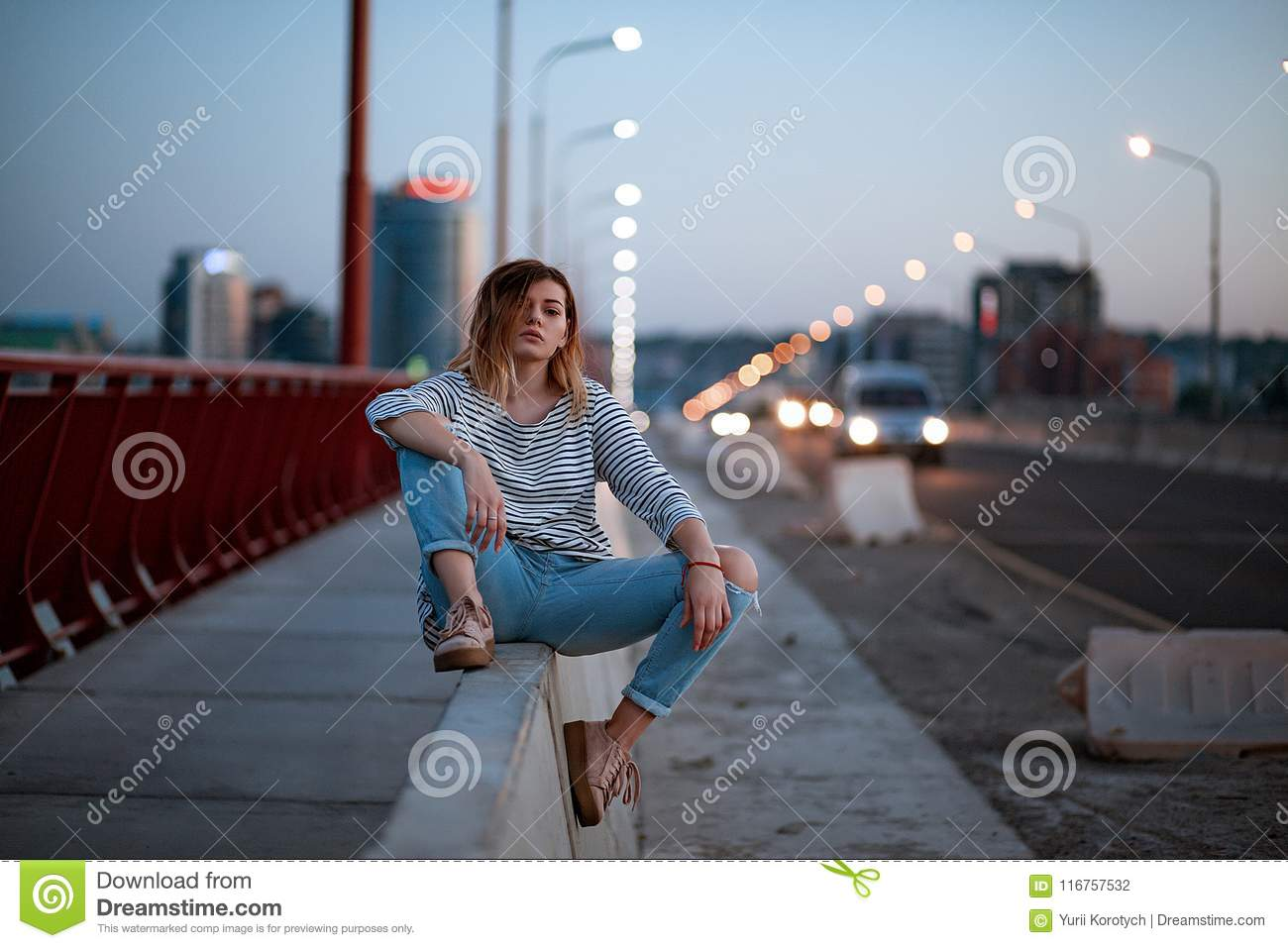 The girl is sitting on the divider near the cars on the bridge