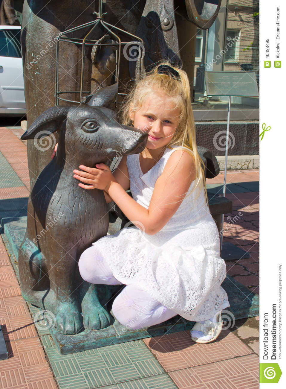 Girl sitting in an embrace with a bronze dog