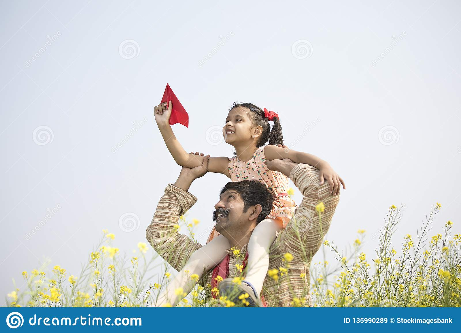 Girl sitting on father`s shoulder and throwing paper airplane