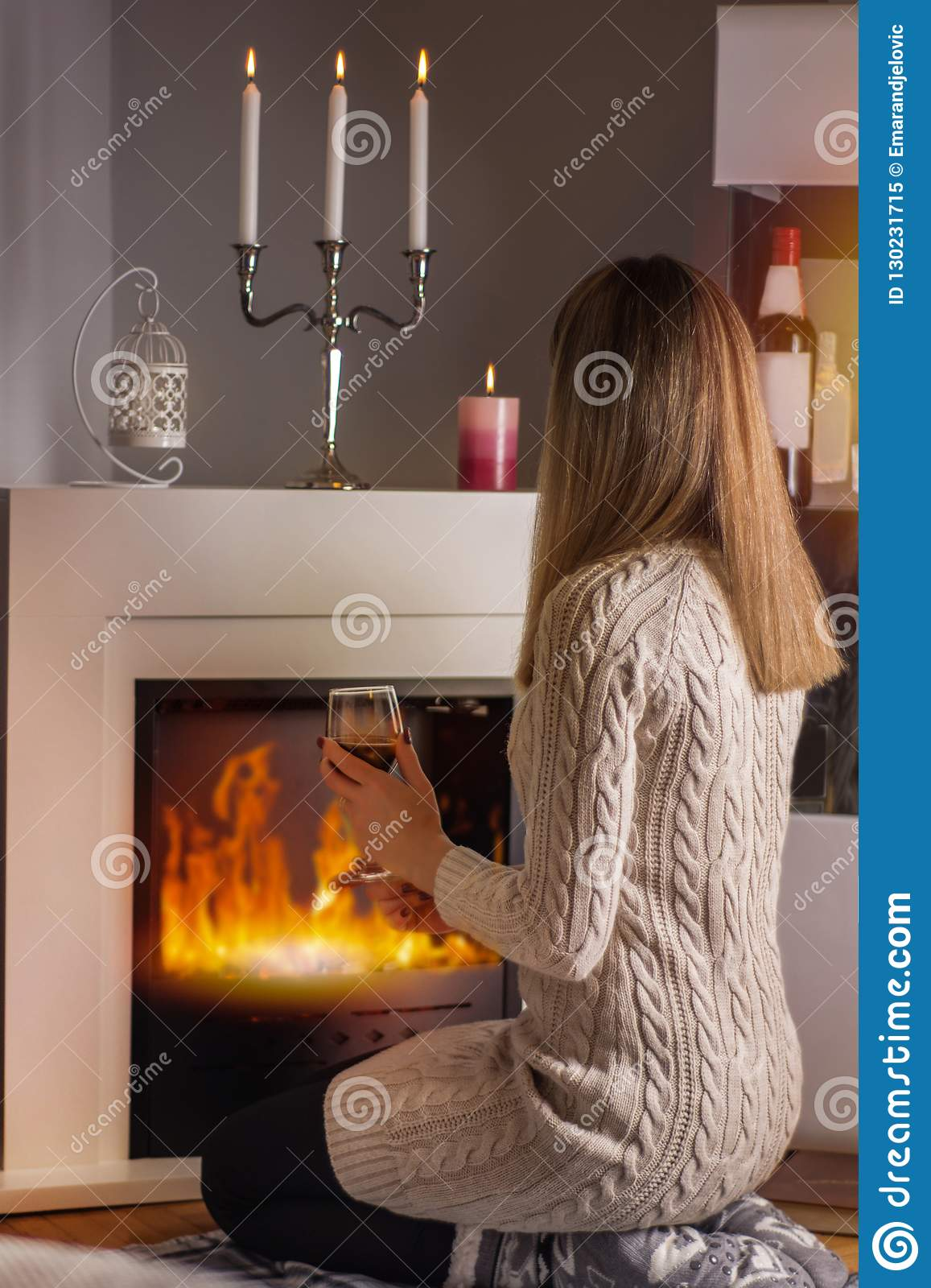 Girl sitting in front of the fireplace and warming with red wine glass in hands