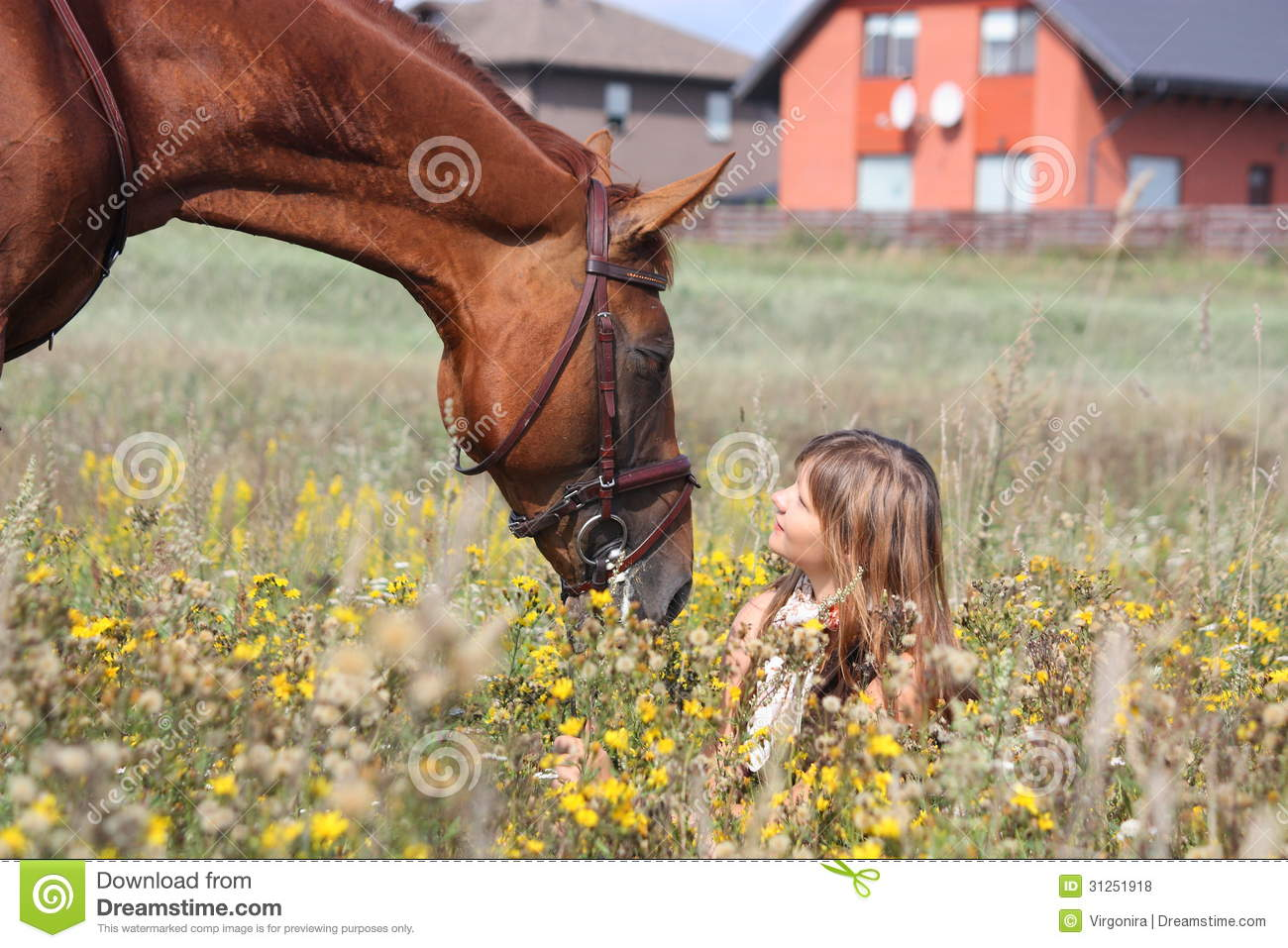 Girl sitting on the ground and chestnut horse standing near