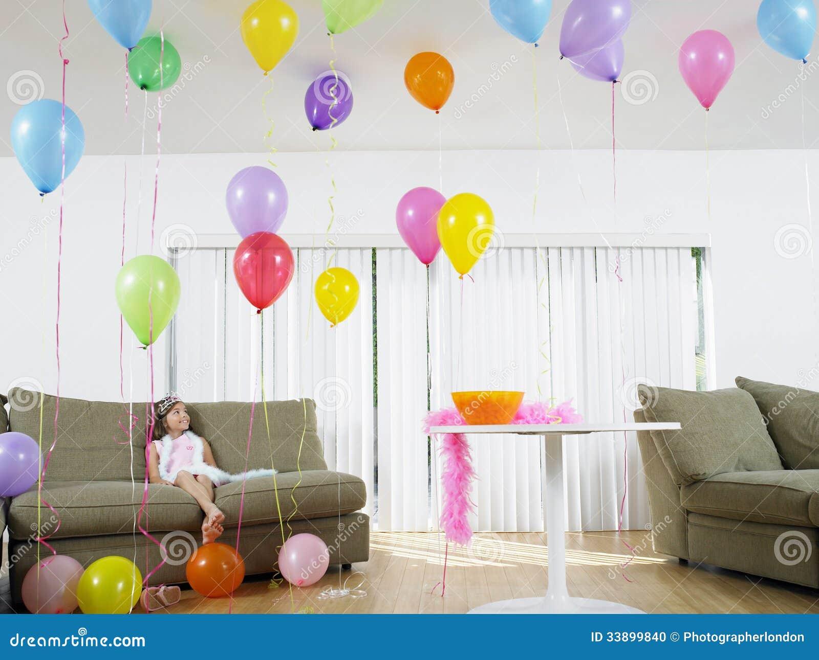 Girl Sitting In Living Room Full Of Balloons Stock Photo
