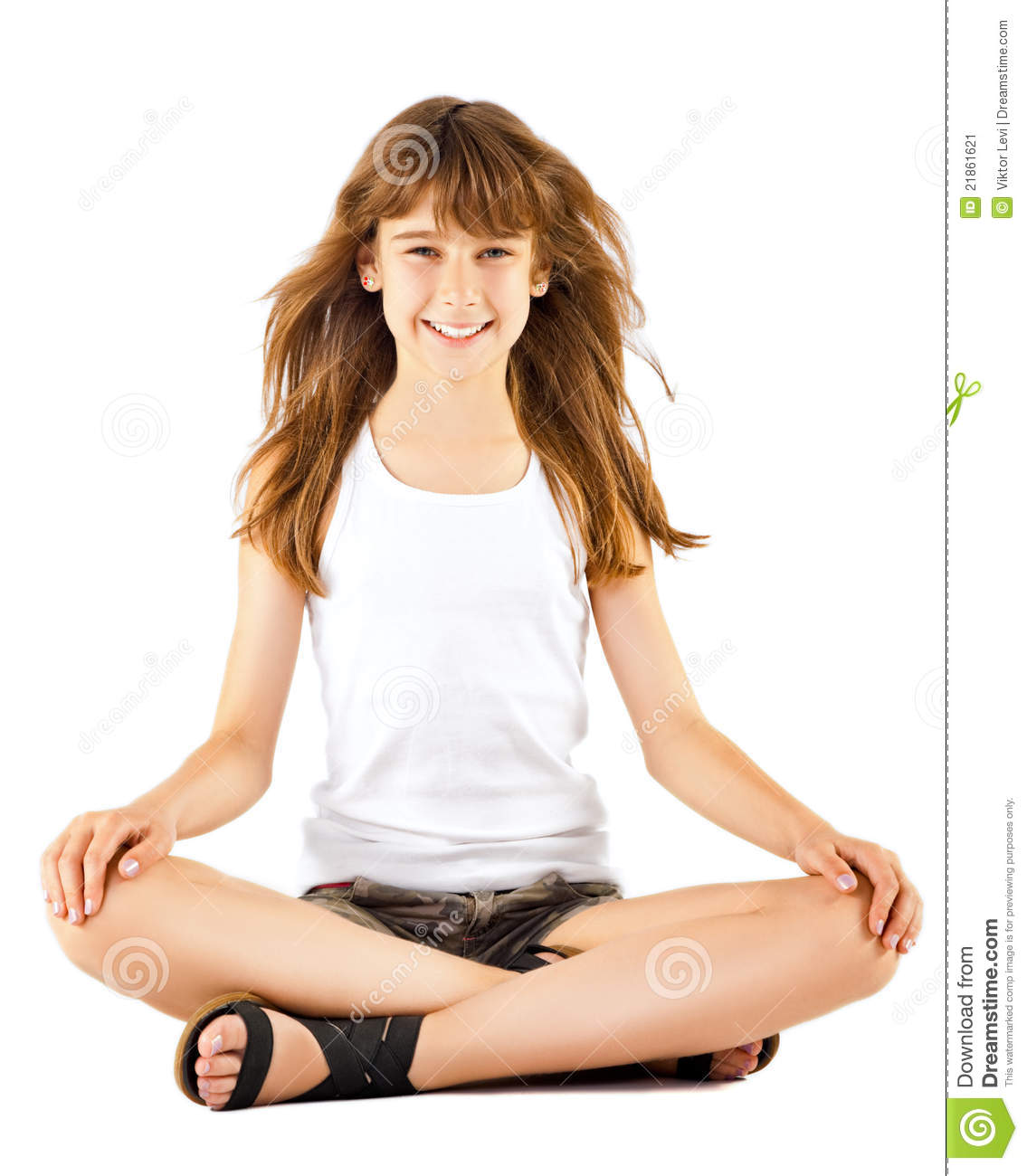 Little girl sitting on the floor in lotus position, looking at camera ...