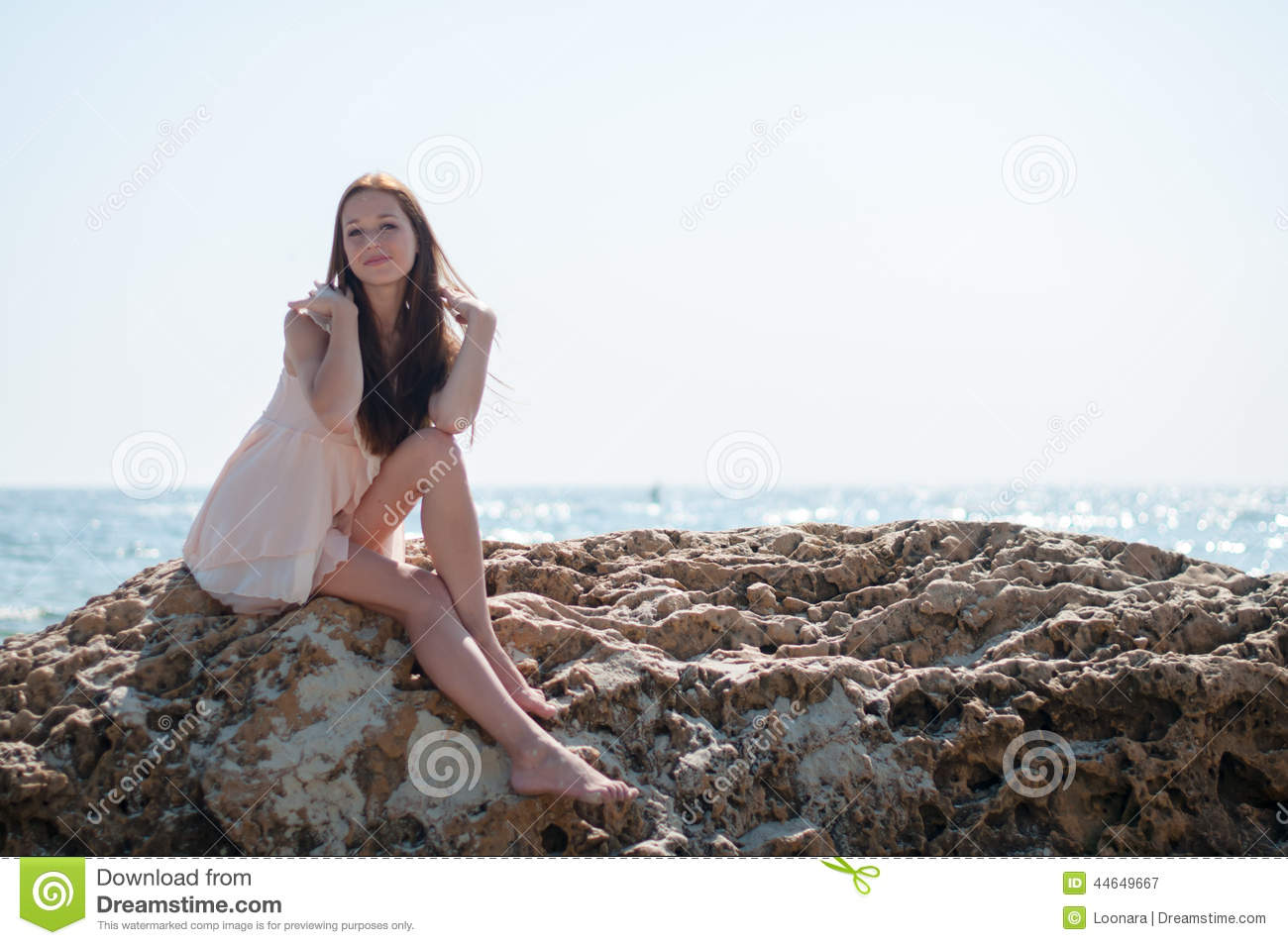 Belle pipe girl sitting on rock