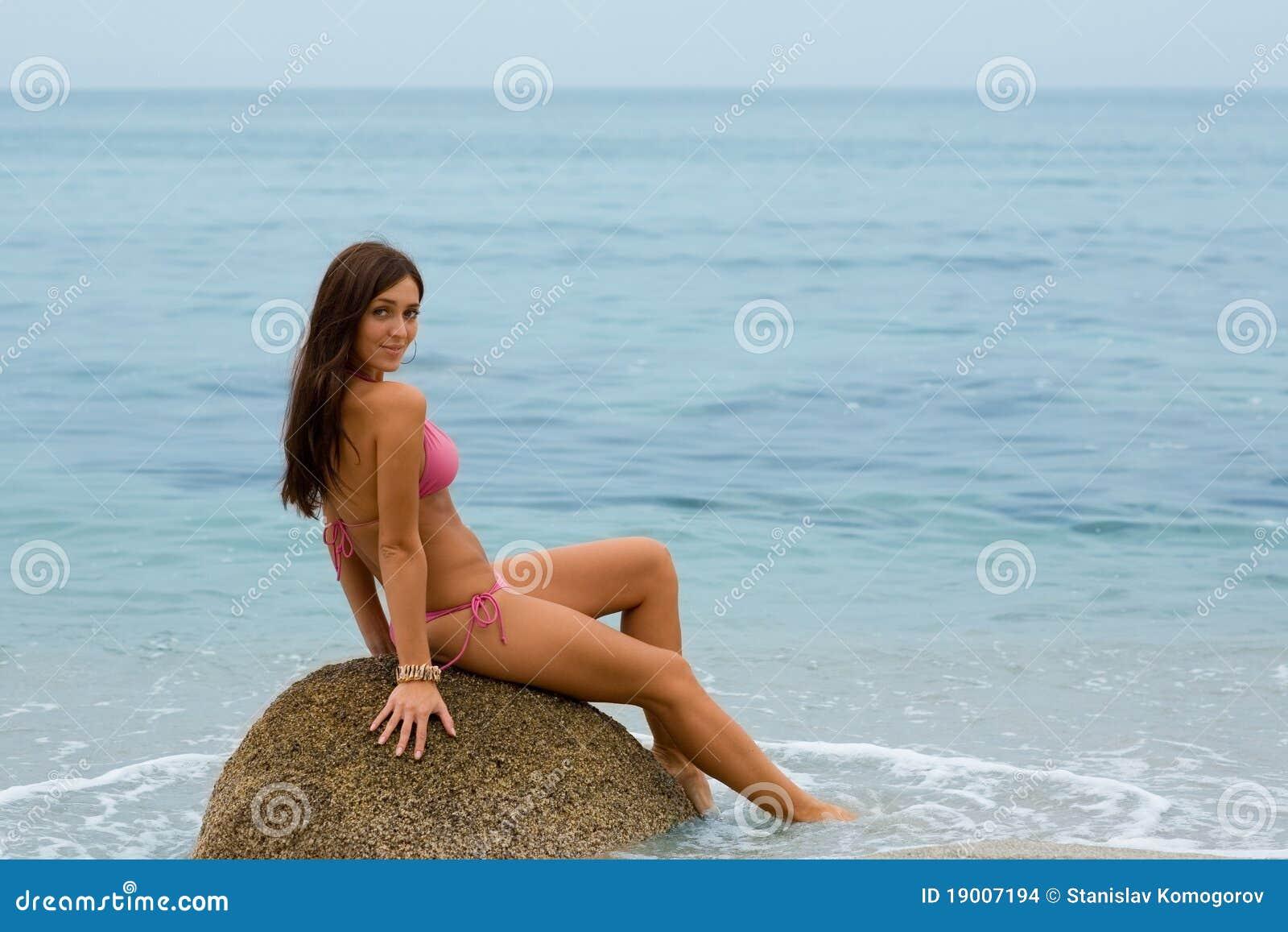 Girl sitting on rock must