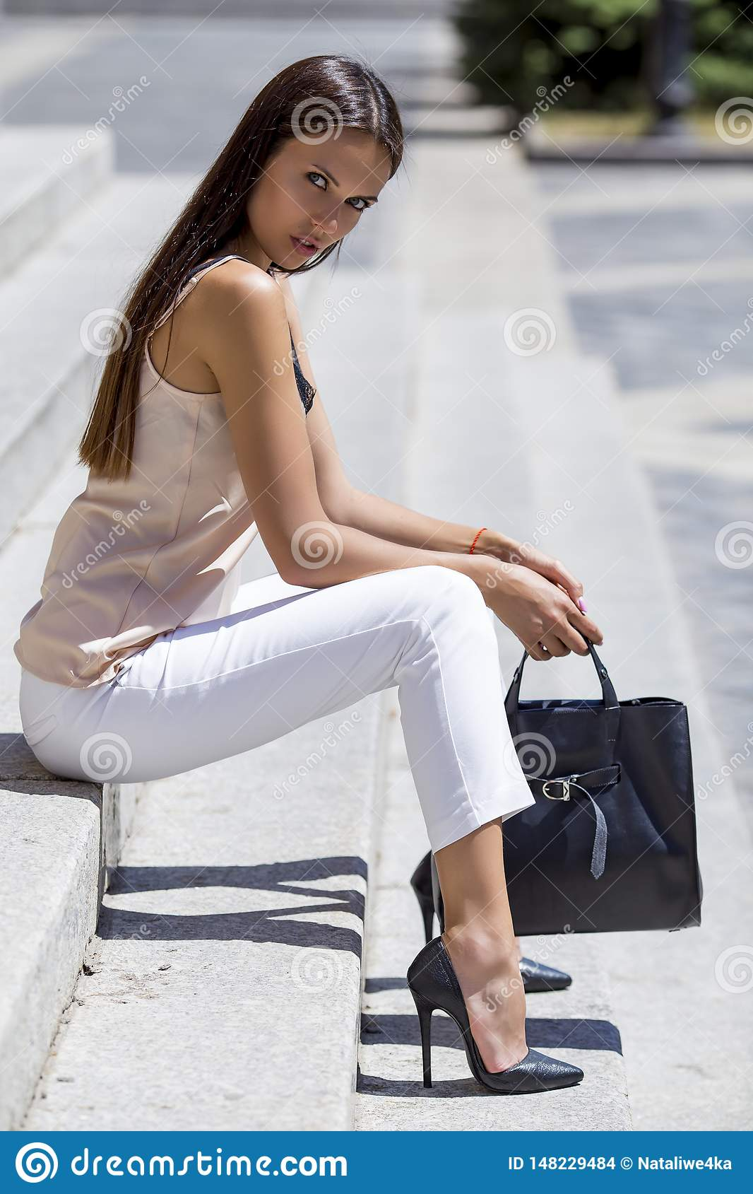 girl sitting on the stairs in chic shoes with a stylish black bag