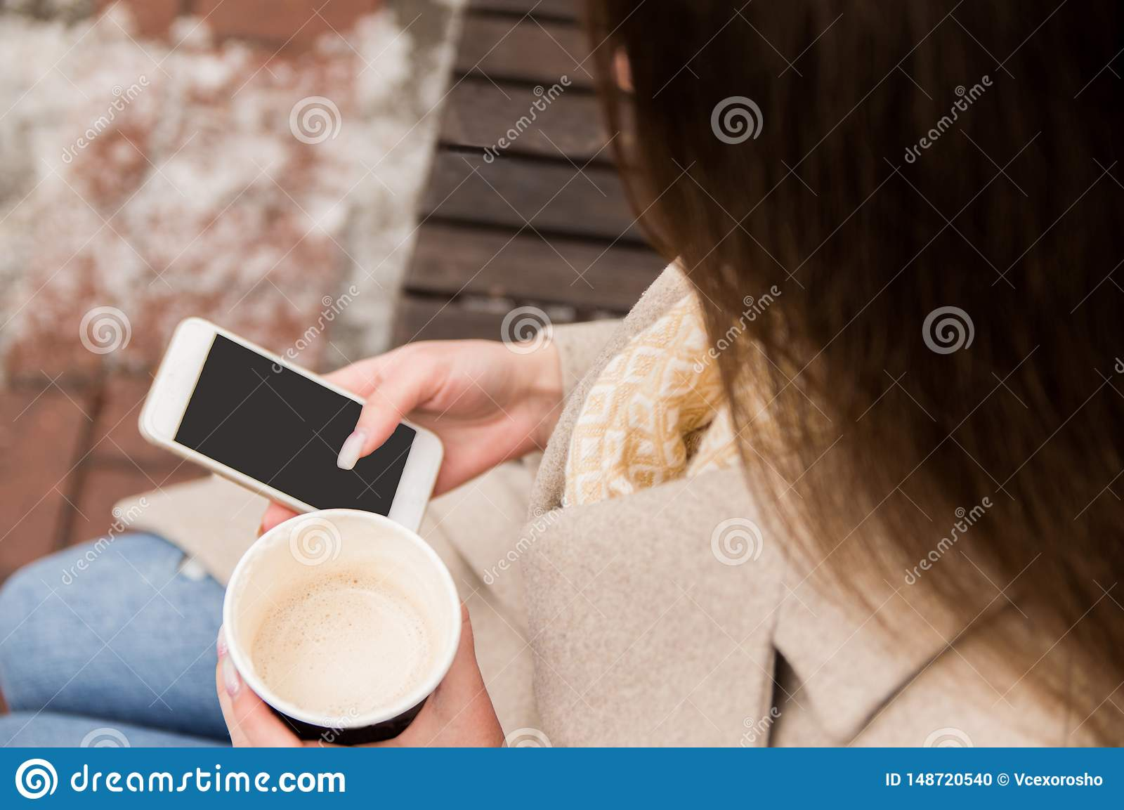 Girl sitting on the street with a phone and coffee in her hands, looking into the phone, waiting for a call, it is winter outside