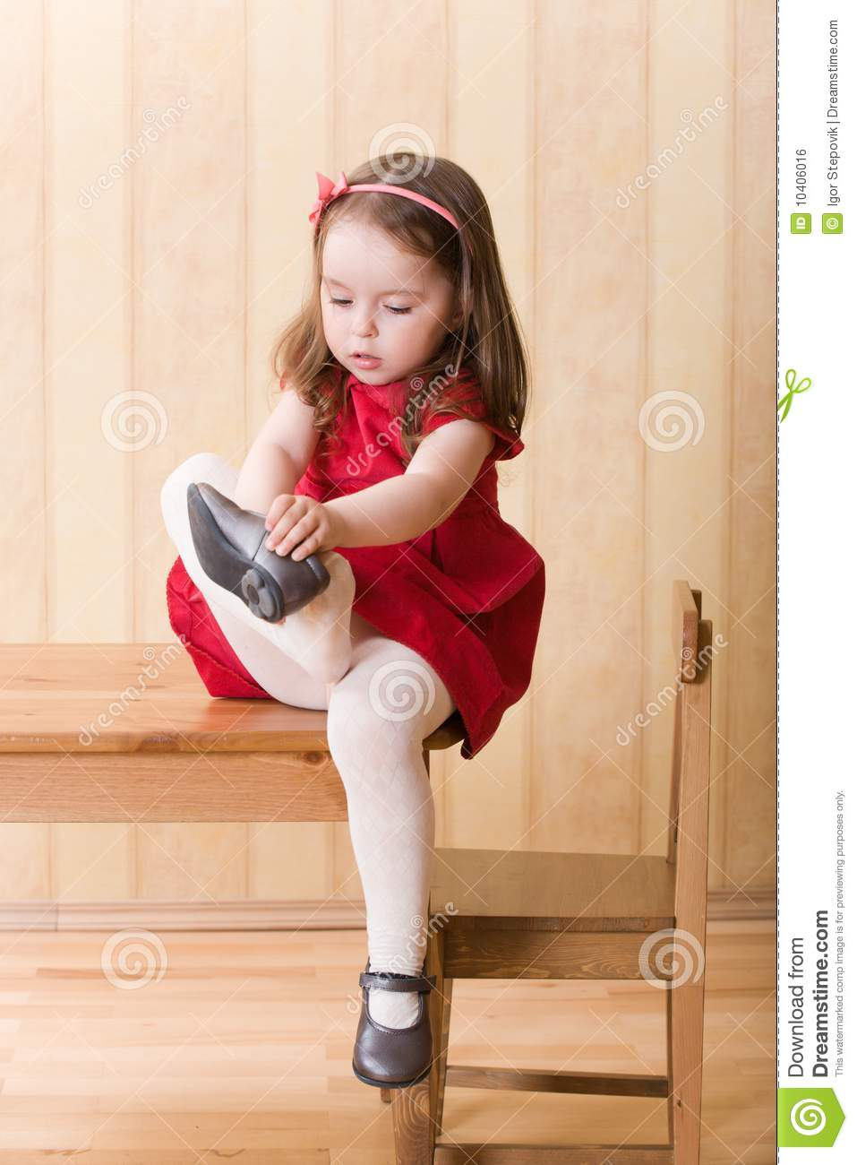 Girl Sitting On Table And Put On One's Shoes Stock Photo ...