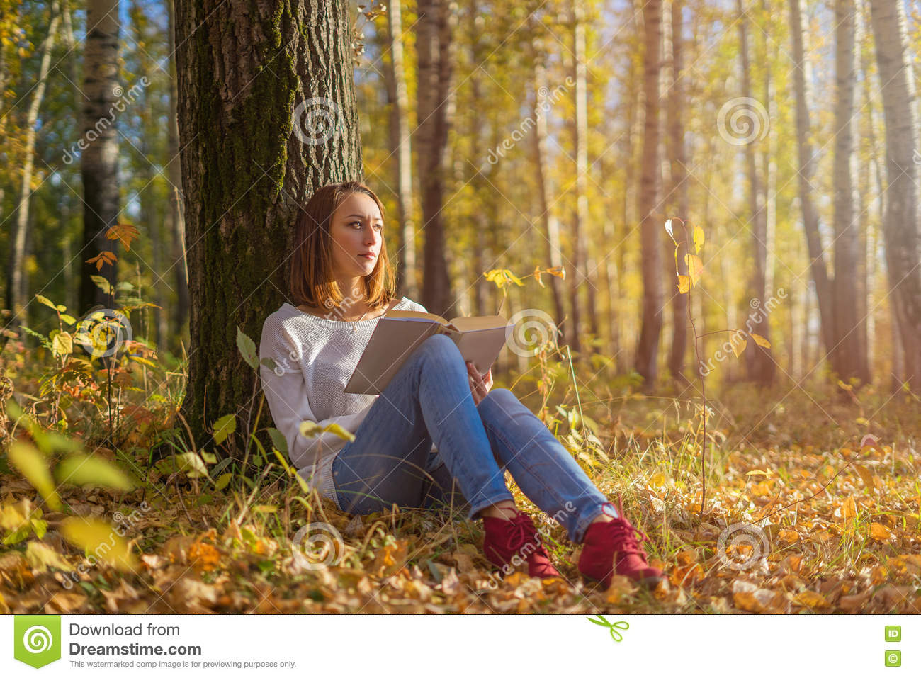 Girl sitting under a tree with a book