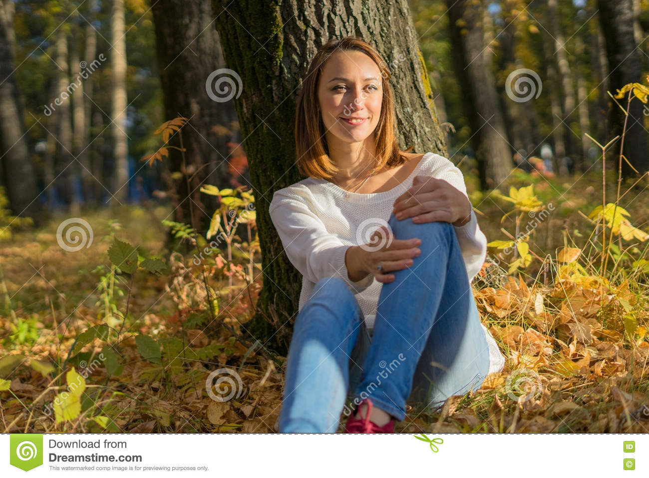 Girl sitting under a tree in the forest