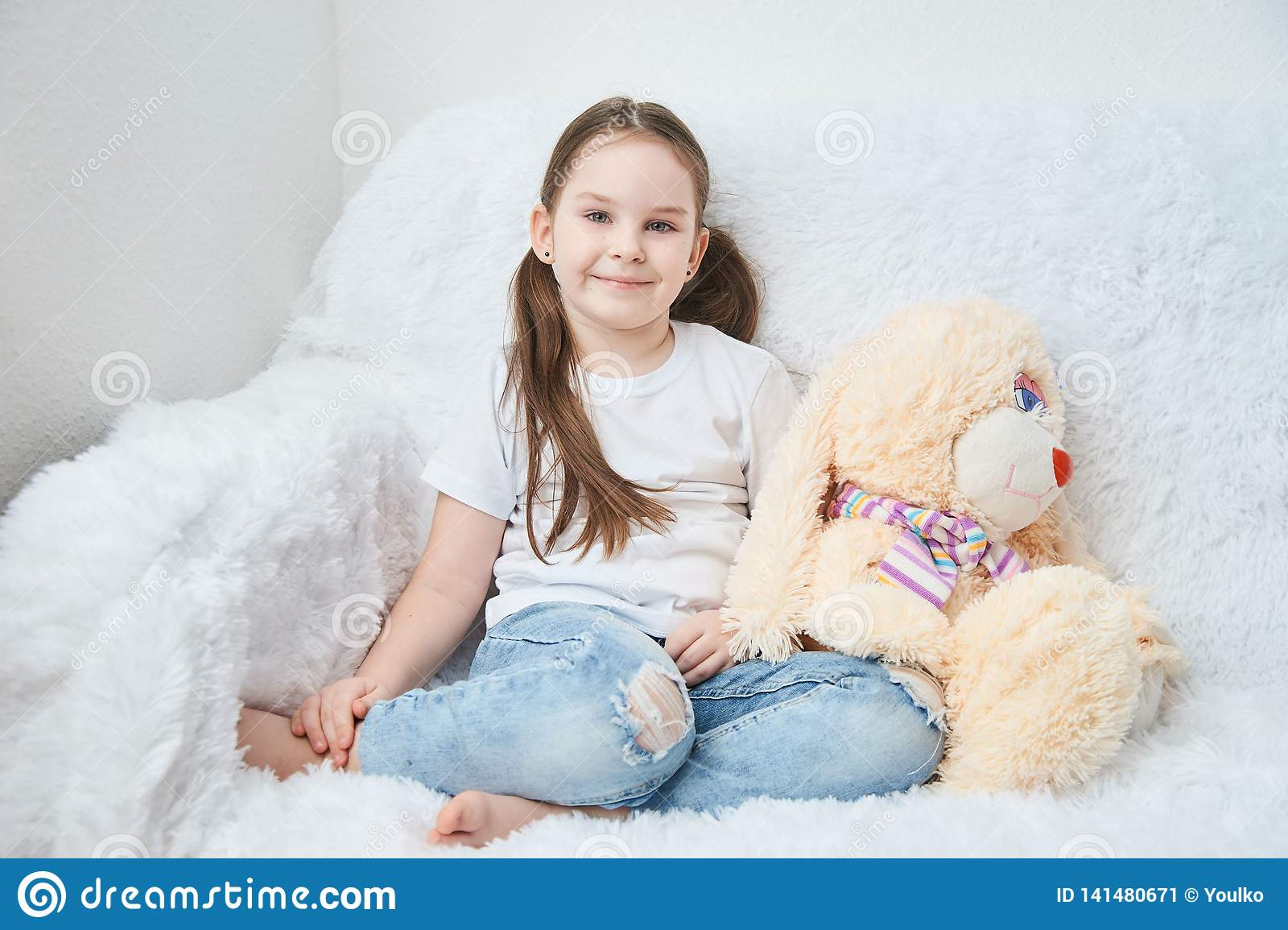 Baby girl sitting on white sofa in white t-shirts and blue jeans. Soft plush banny