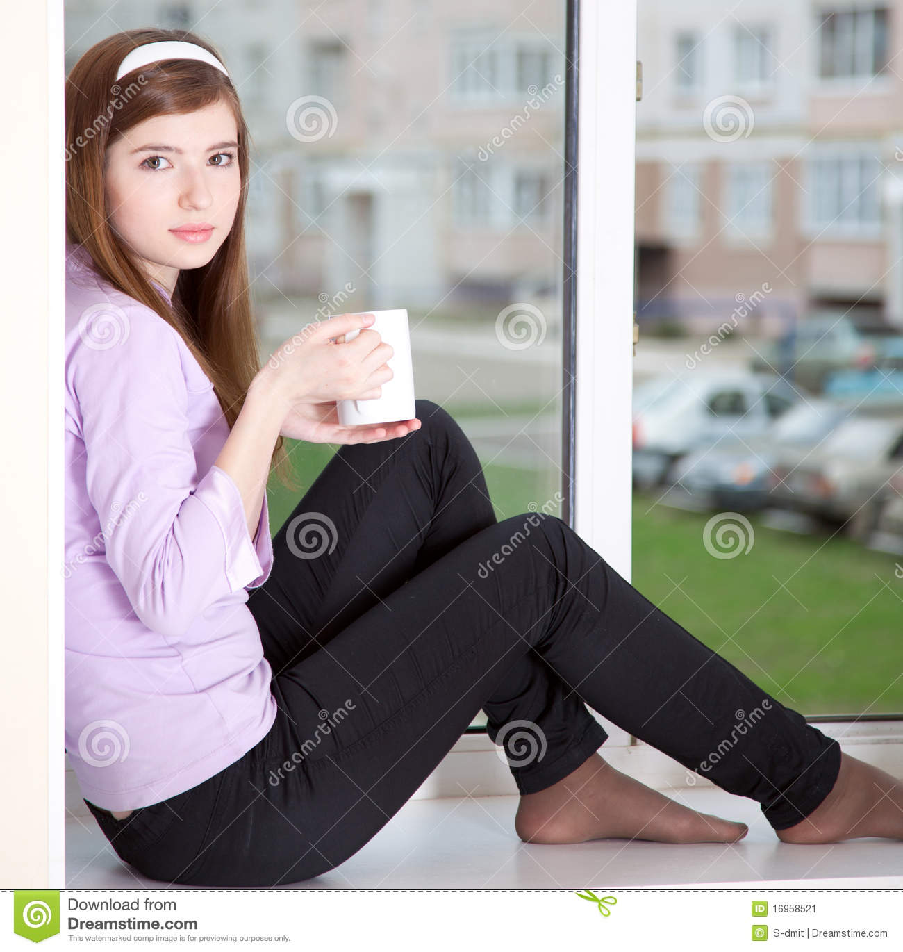 16 Attractive Window Seat Designs For Pleasant Relaxation: A Girl Is Sitting On The Window-sill Stock Image
