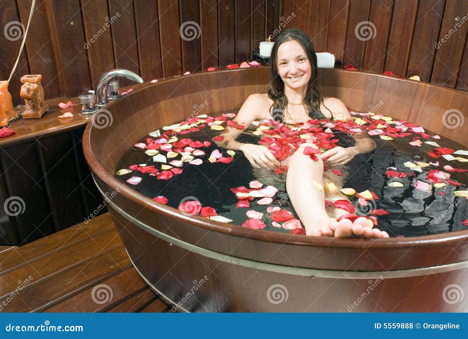 girl sitting in wooden bathtub