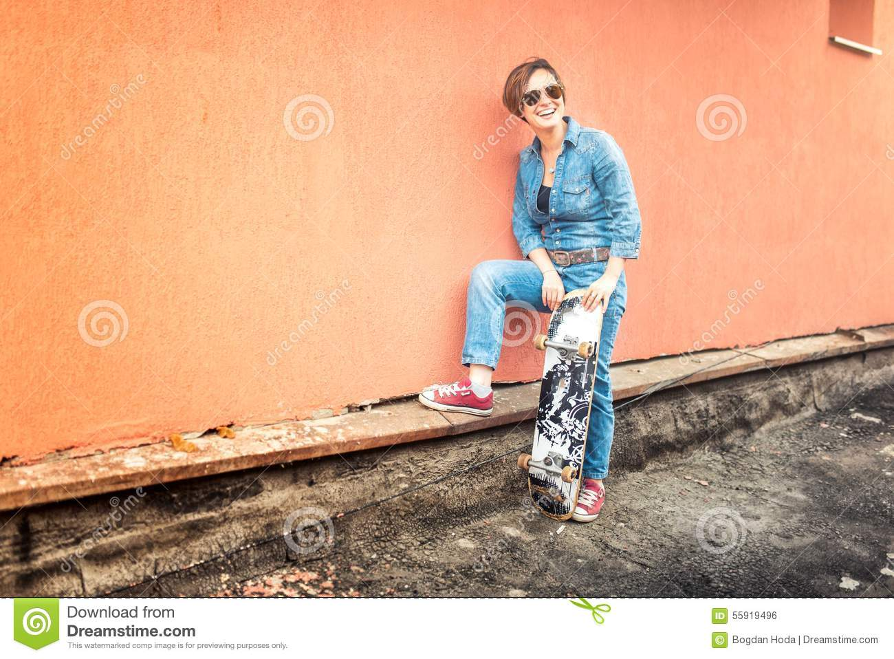 Girl with skateboard and sunglasses living an urban lifestyle. Hipster concept with young woman and skateboard, instagram filter
