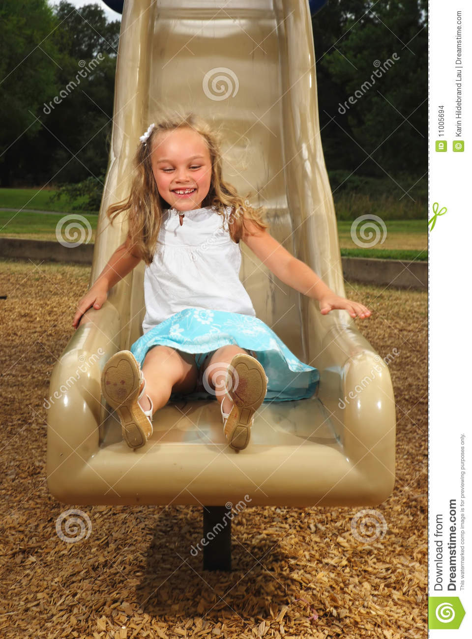 Oung girl sliding down a playground slide in summer.