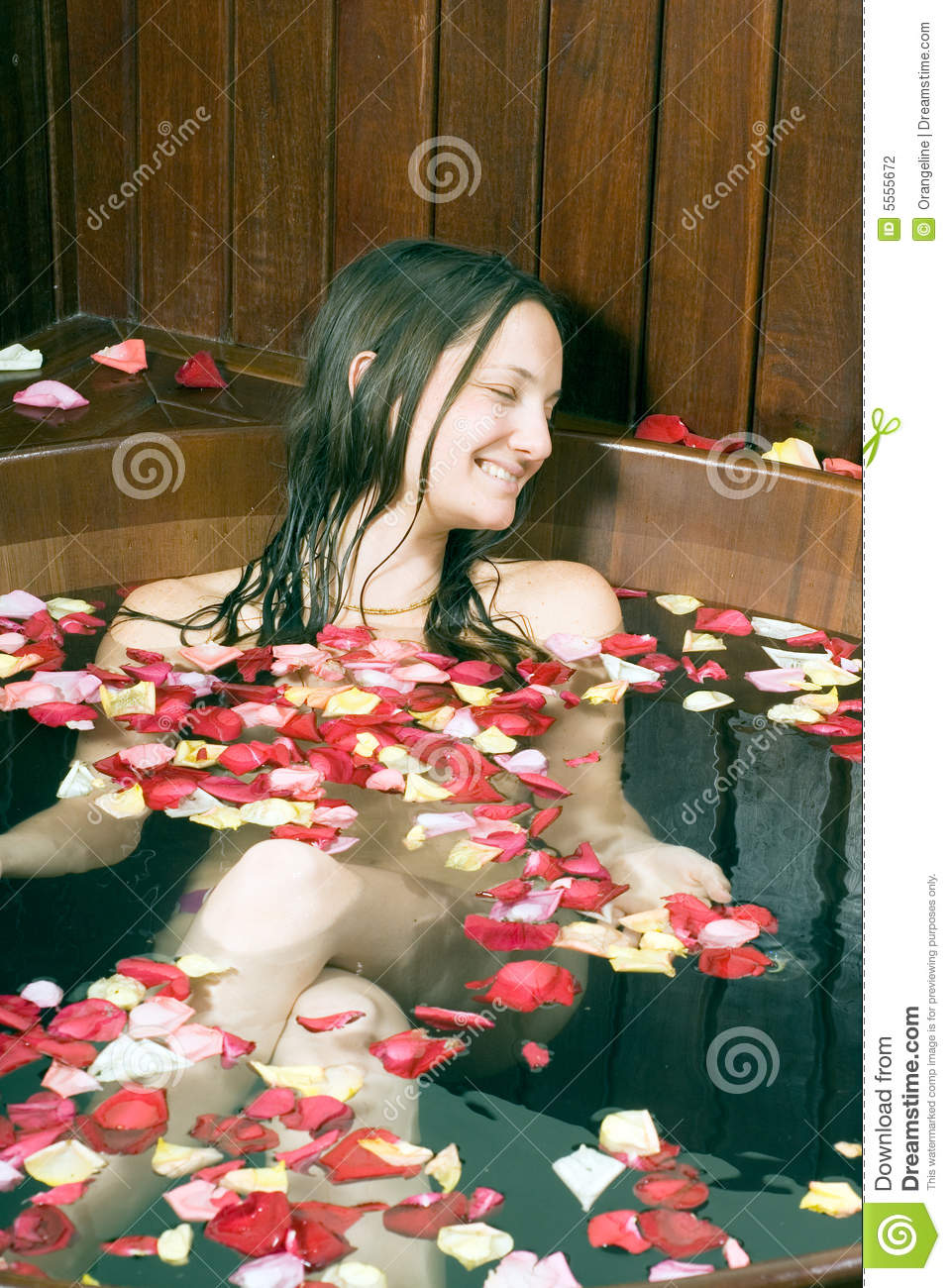 , young girl sitting in a bathtub with rose petals floating, smiles ...