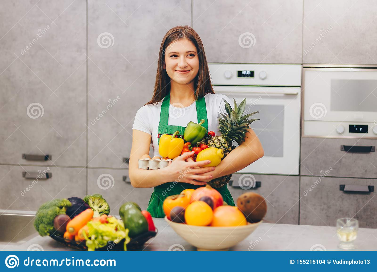 A girl smiling holding nutritious fruit and veg