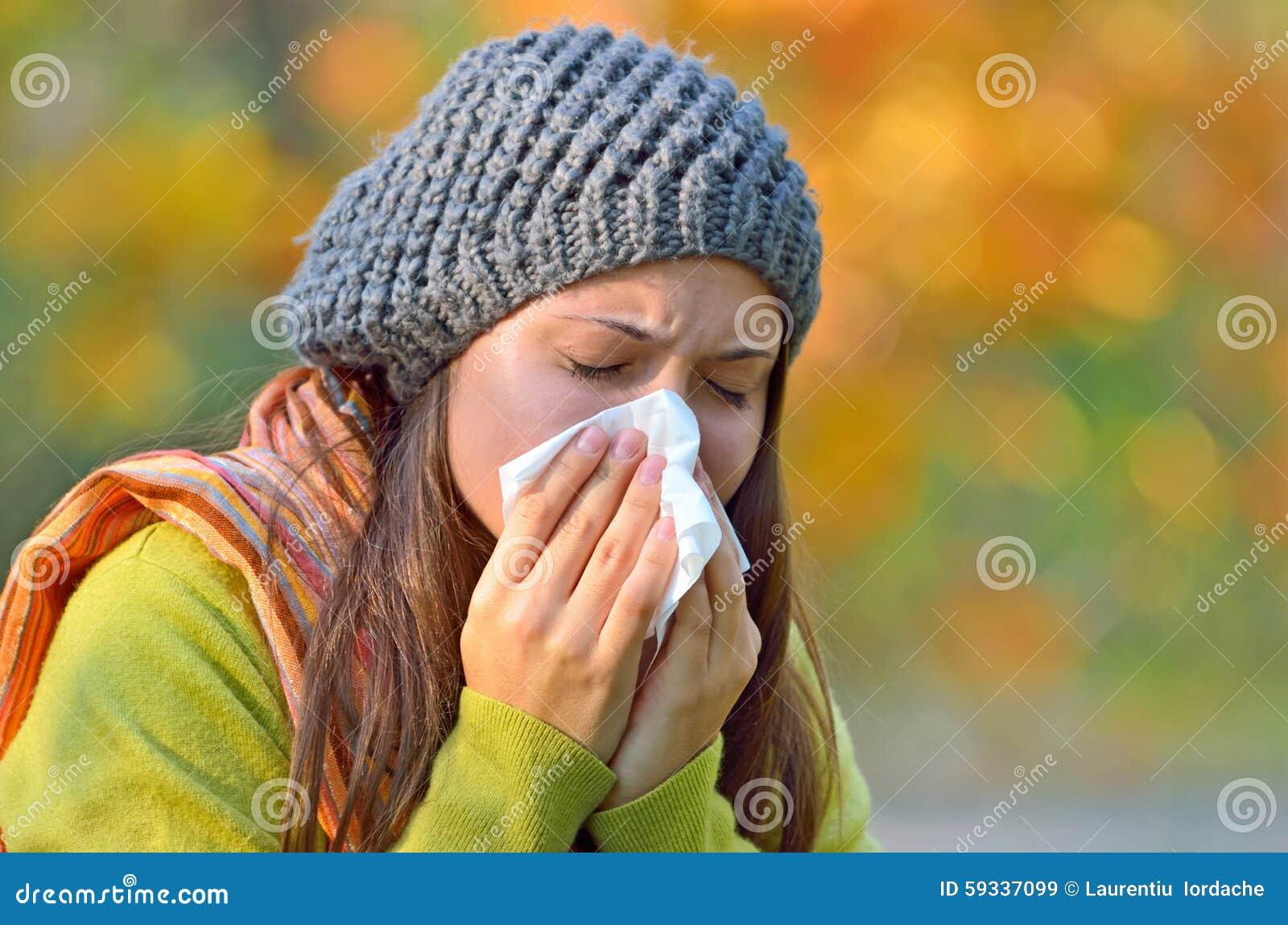 Girl sneezing in tissue.