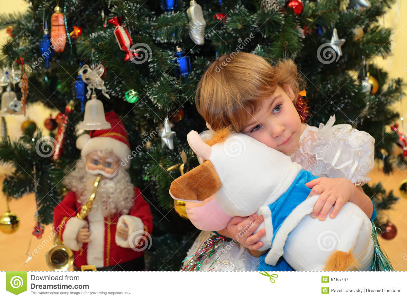 Girl with soft toy under New Year`s tree