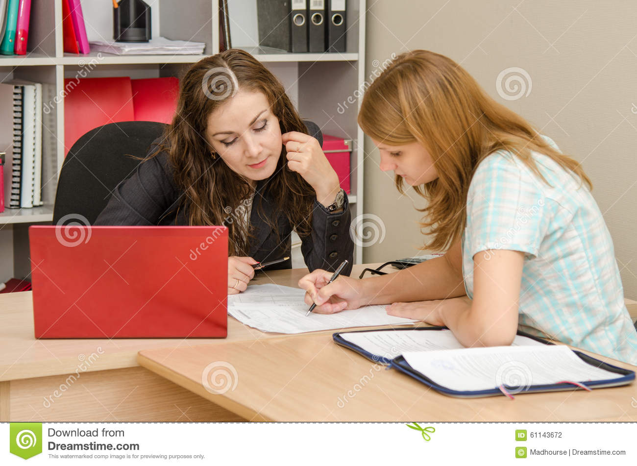 Girl and specialist office editing text in a paper document