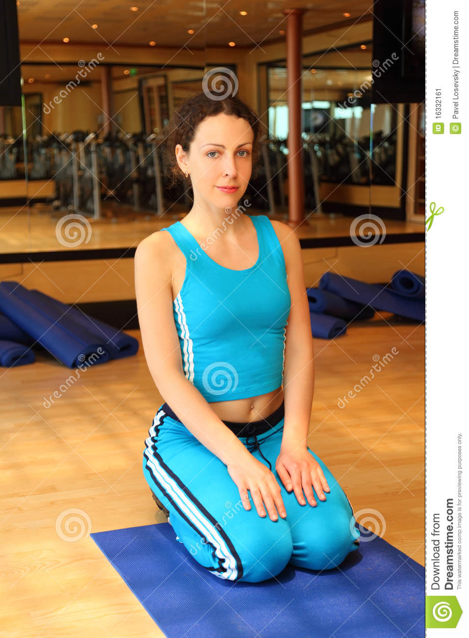 Girl In Sport Dress Sitting On Mat In Gym Stock Image