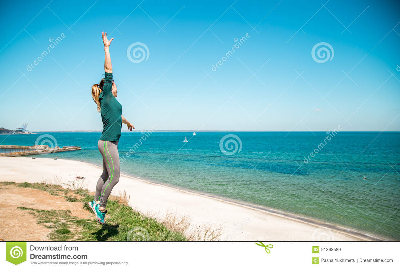 Girl In Sportswear Fitness By The Sea Listening Stock Image