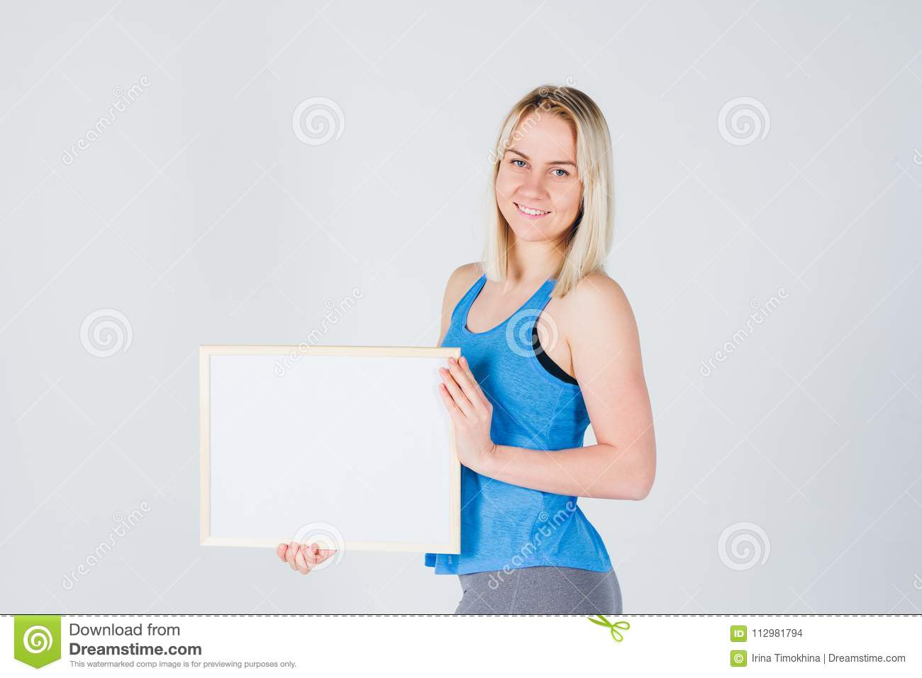 Girl in sportswear holding a frame with an ad