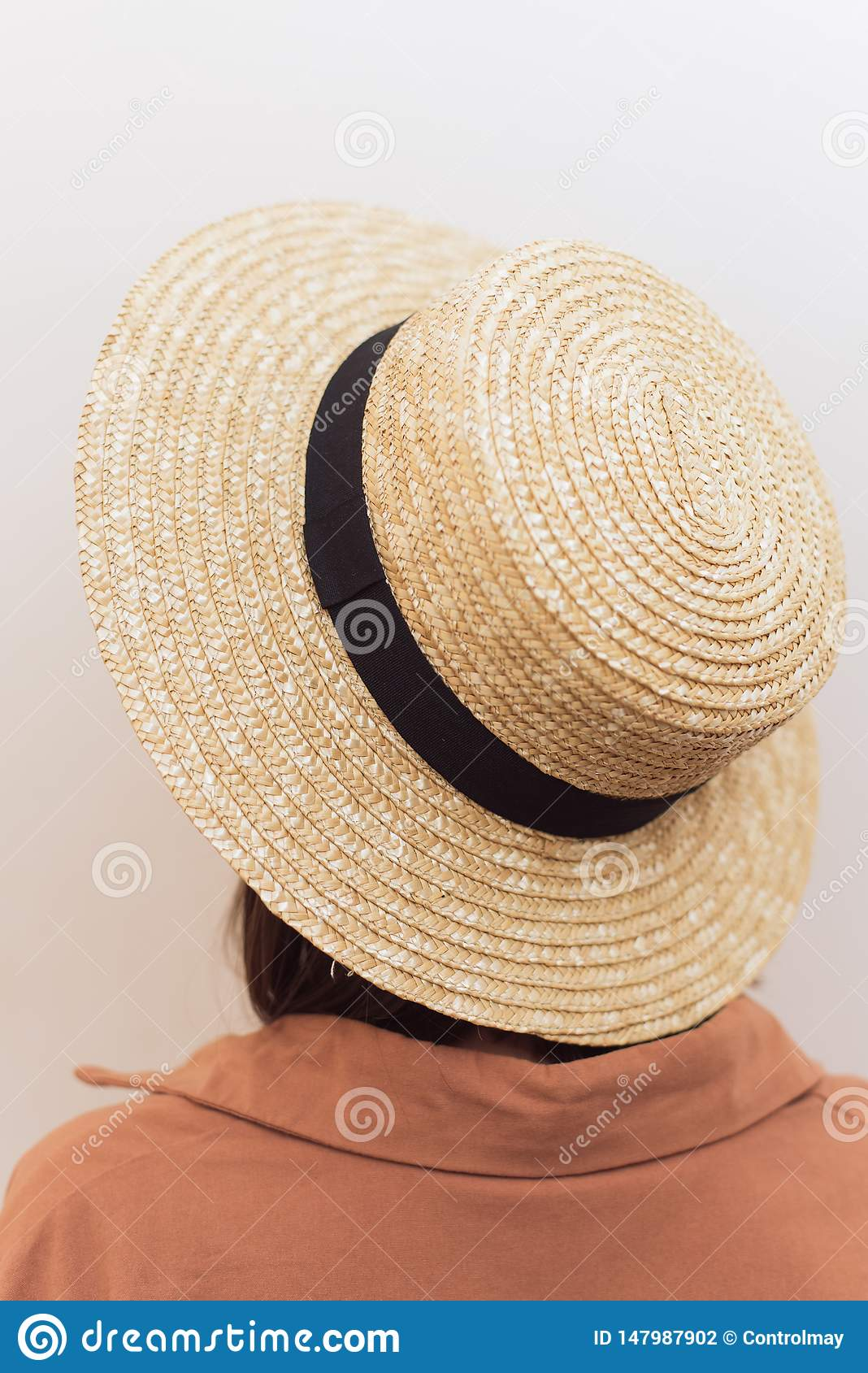 Girl with a square in a straw hat on a white background.