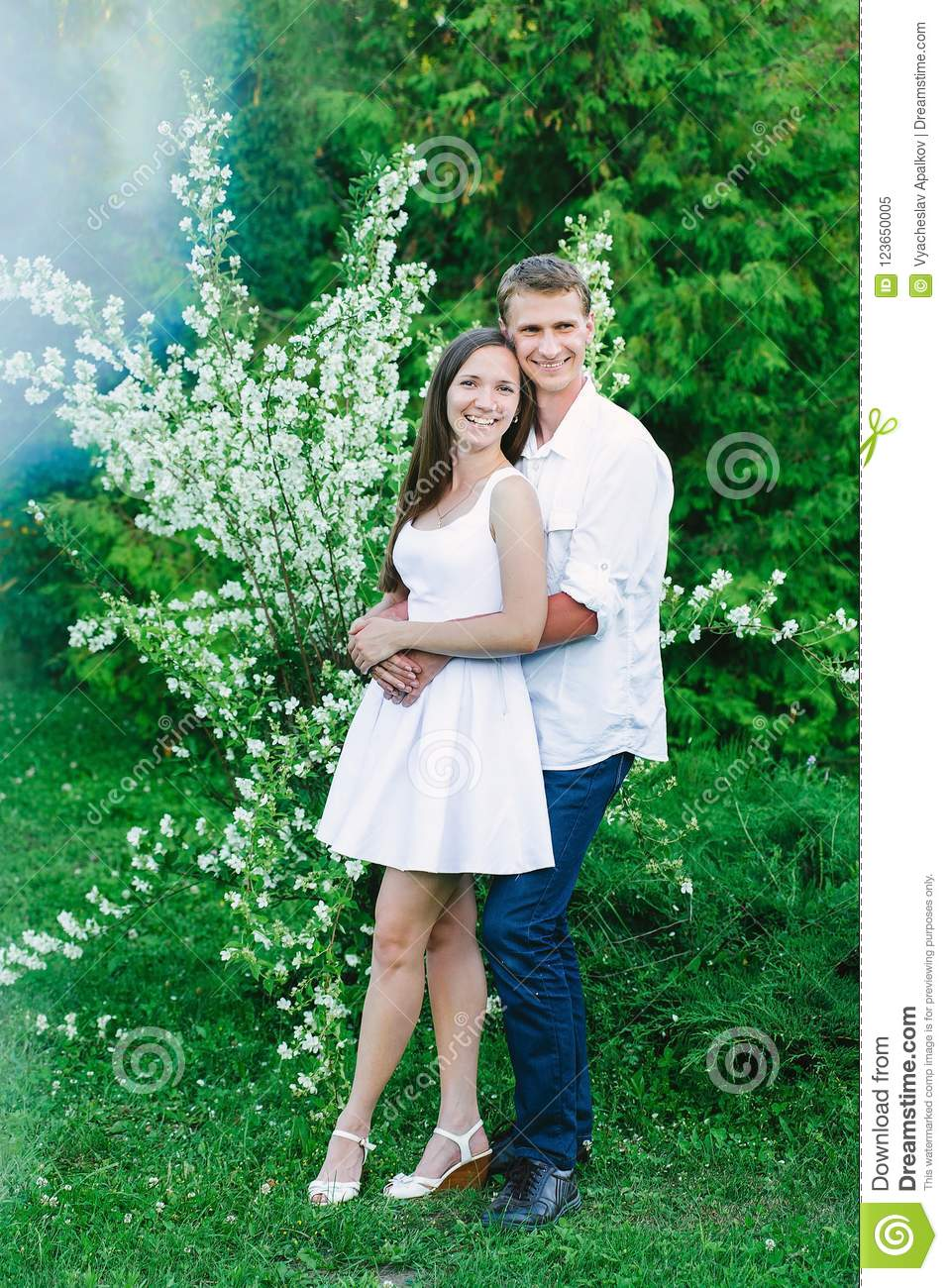 Girl standing back to her hugging man