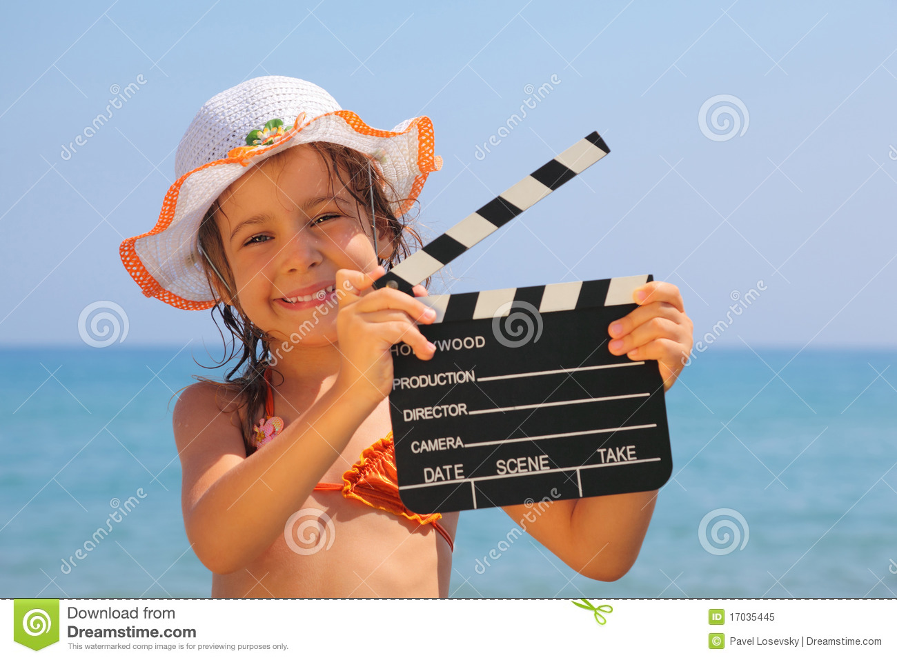Girl standing on beach and holding clapboard