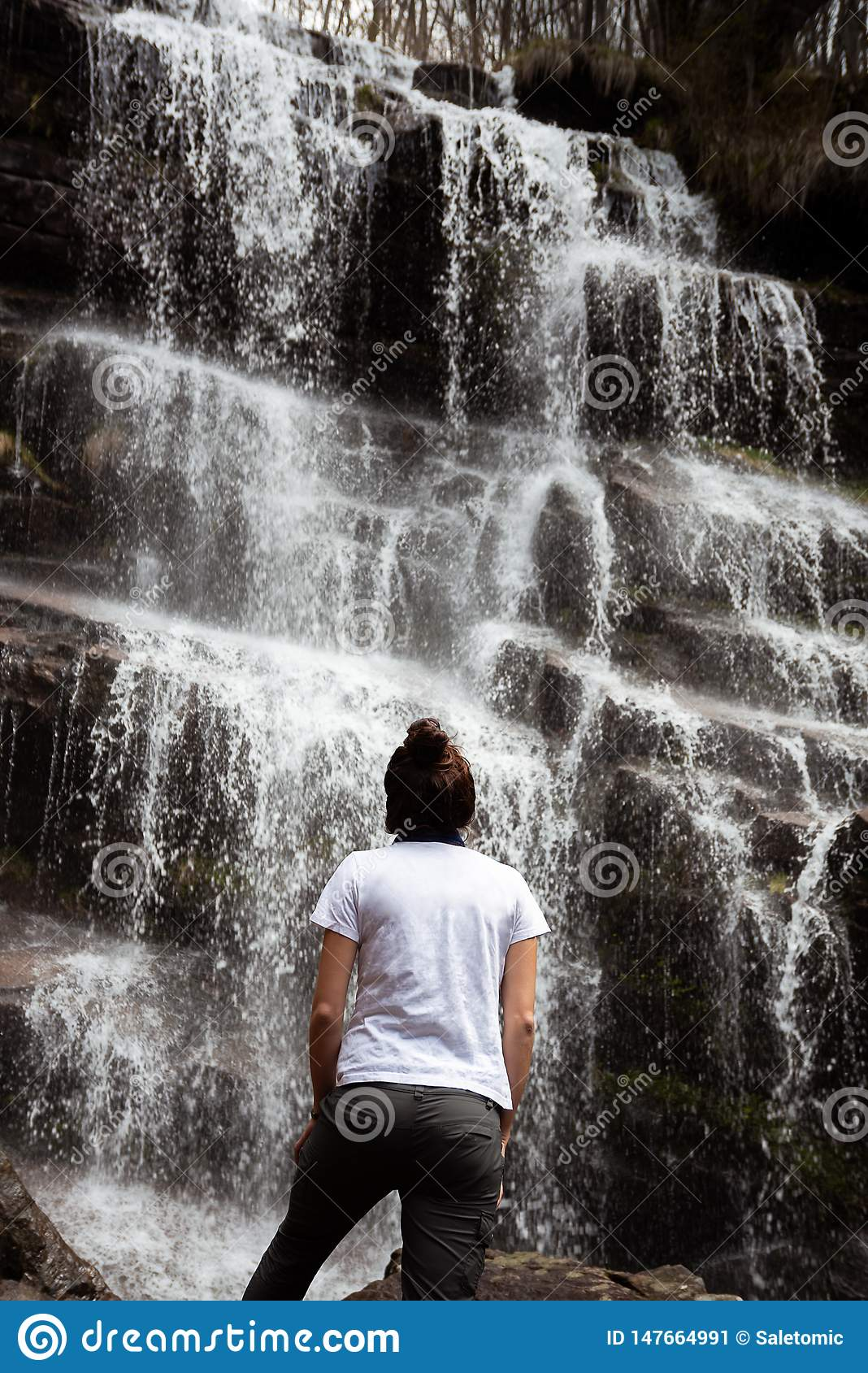 Young Traveler Woman At Waterfall In Tropical Forest. View