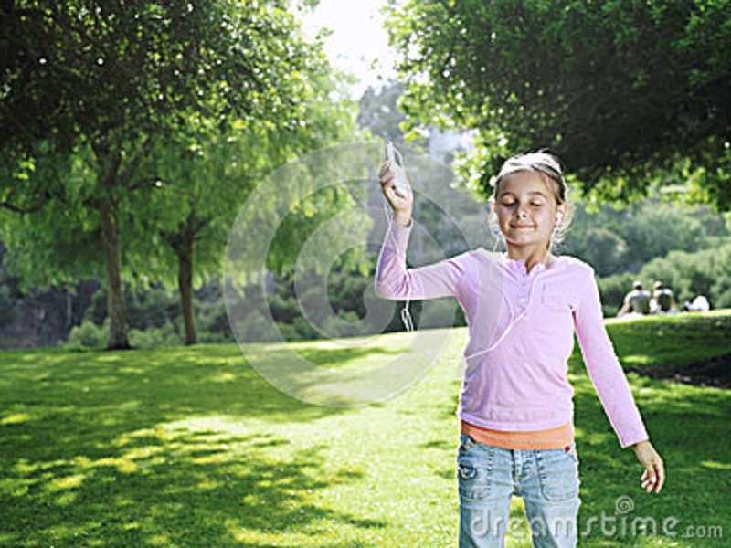 Girl (7-9) standing on grass in park, listening to MP3 player, eyes closed, smiling