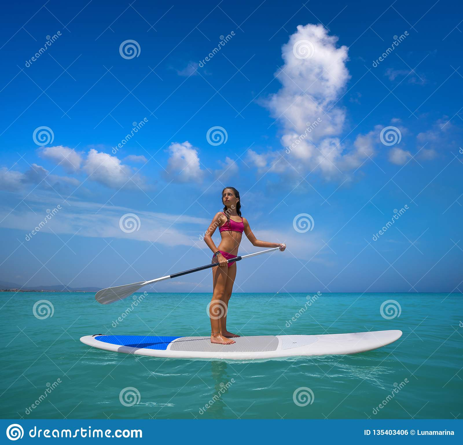 Girl standing on paddle surf board SUP