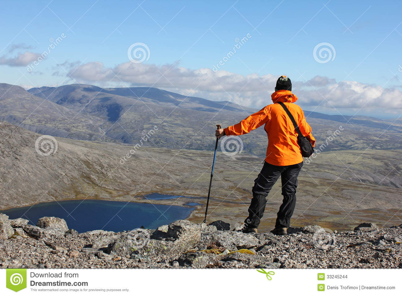 Girl standing on top of a mountain and looking on the lake russia