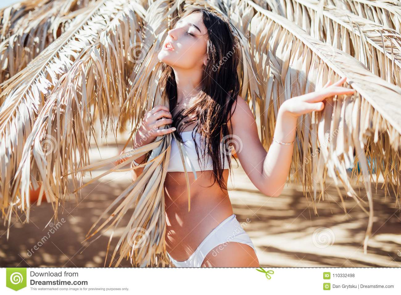 Girl standing under a wooden umbrella on the beach. Young woman resting at beach near the sea. Summer time