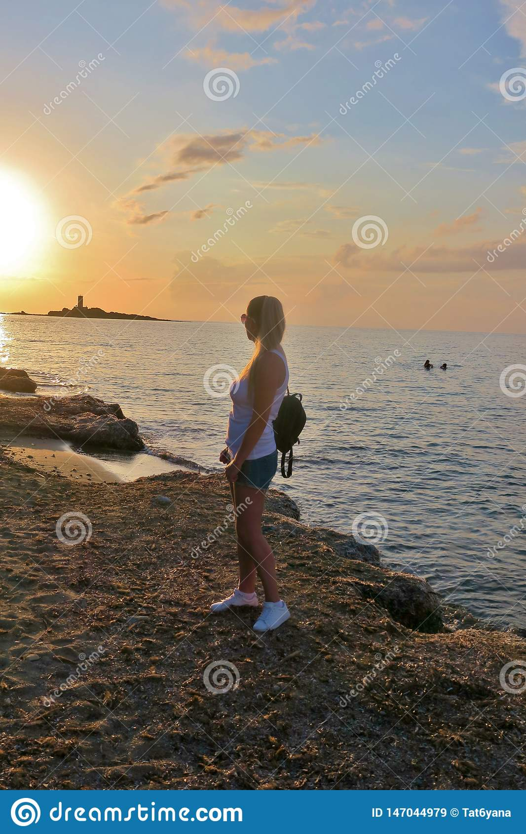 Girl stands on the seashore and looks at the beautiful sunset