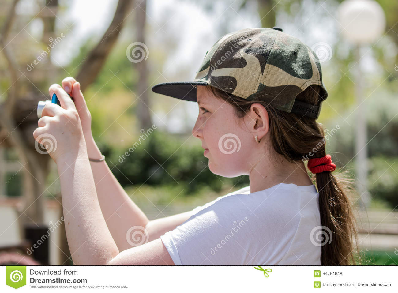 Girl stands on a sunny day and learns to take pictures with a camera