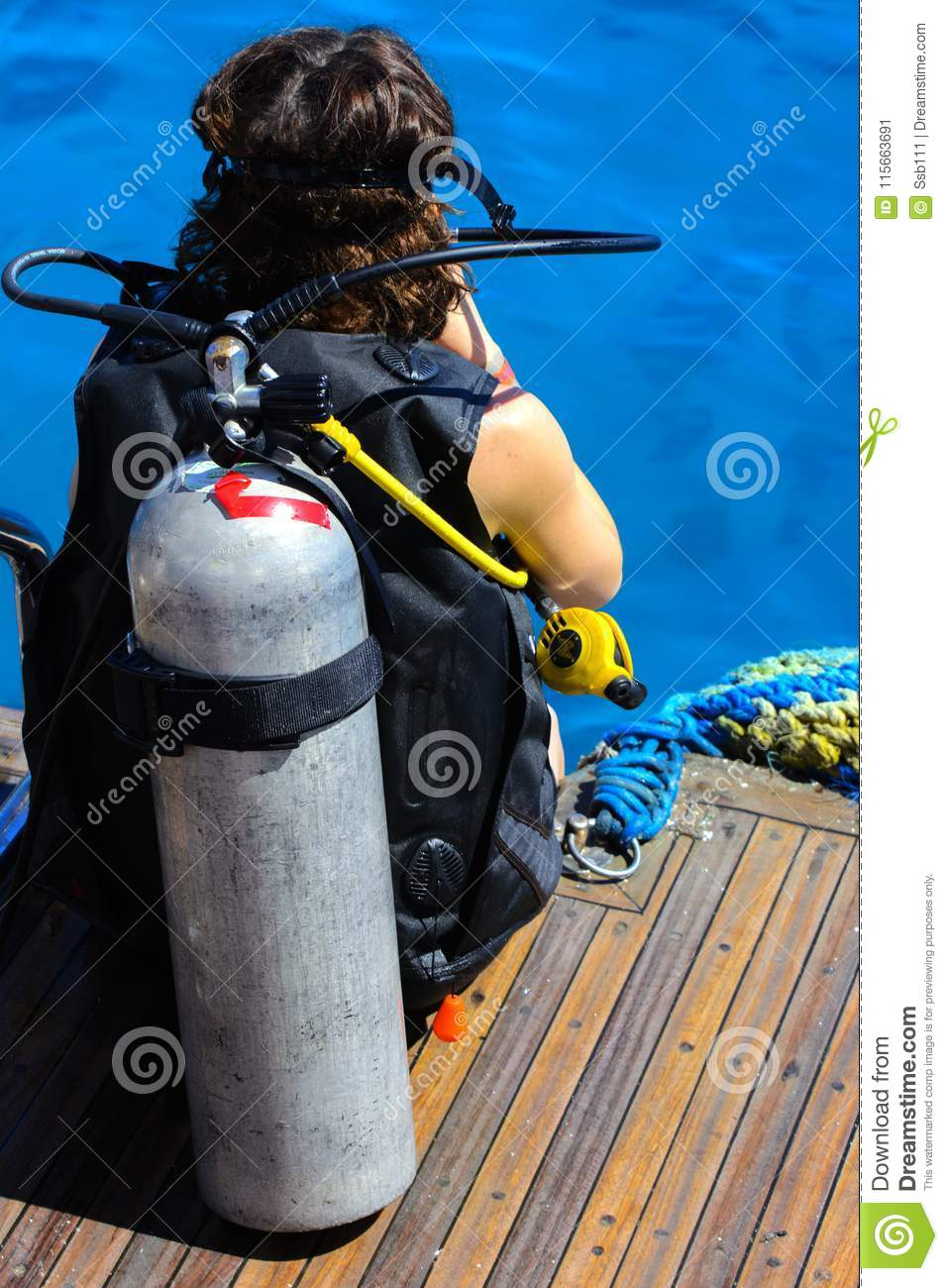 A girl at the stern of a ship in a diving suit prepares to immerse herself in a transparent and turquoise Red Sea