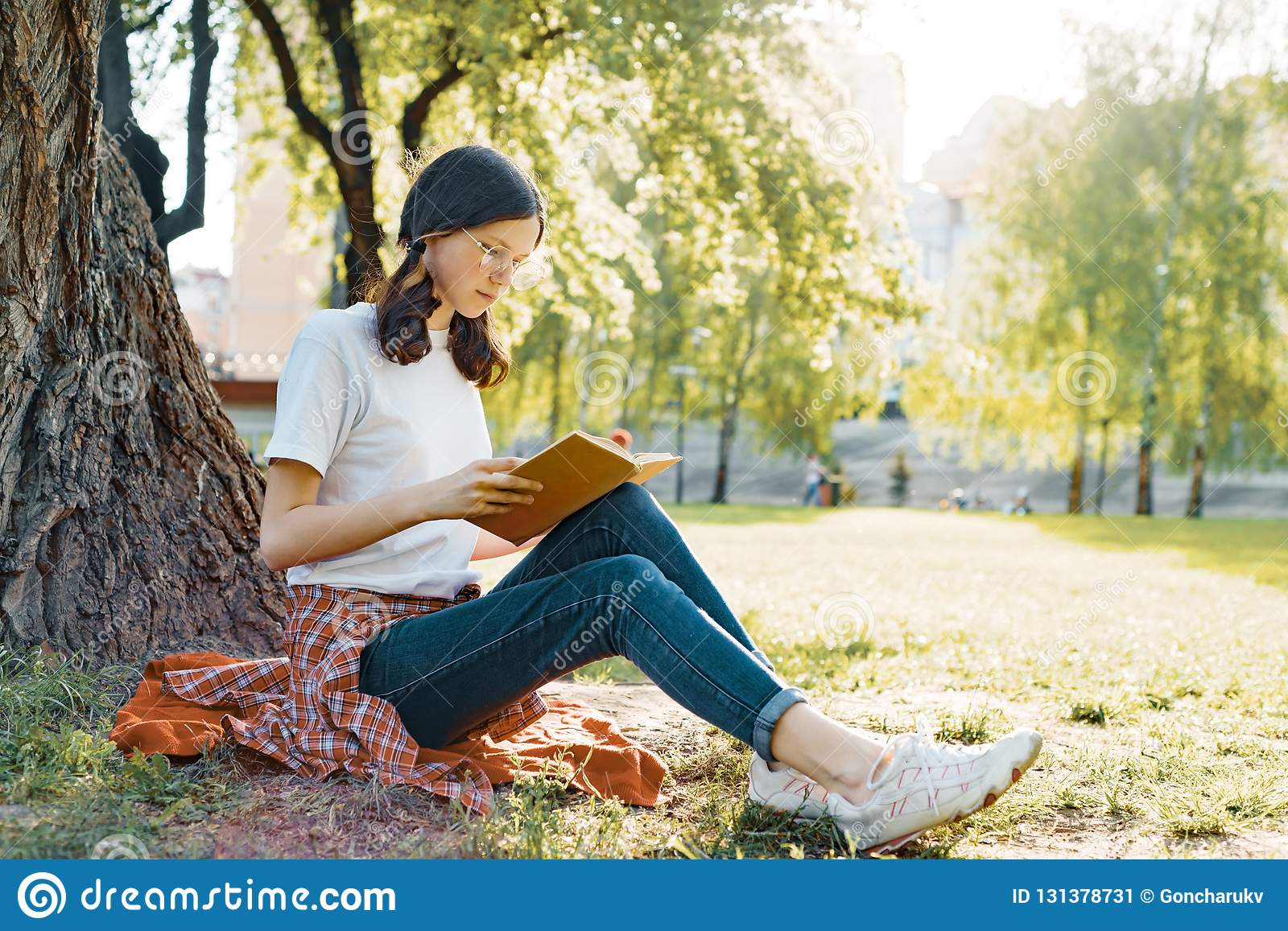 Girl student in glasses reading a book in the park sitting under a tree on the grass