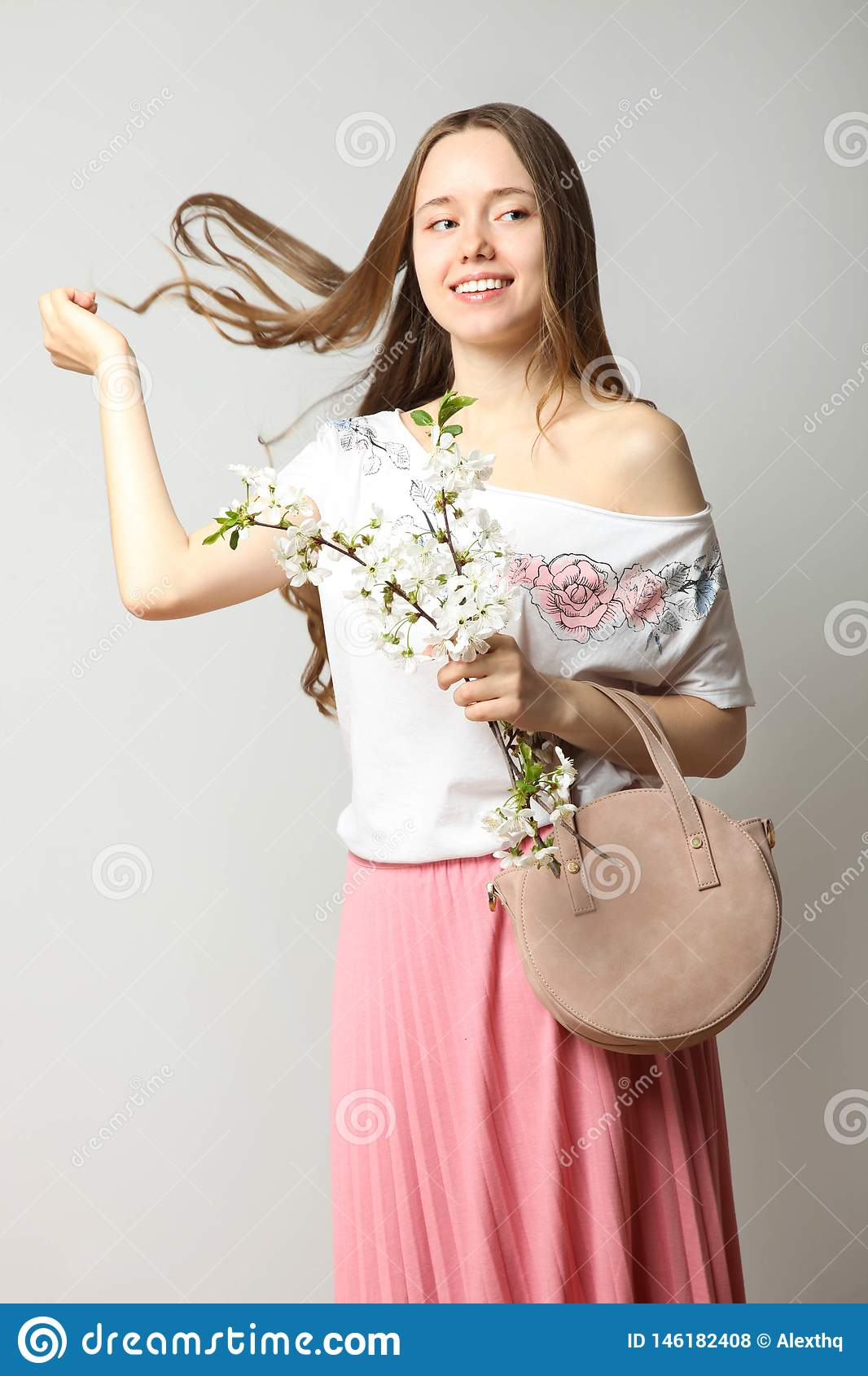 Girl in stylish spring clothes with fashionable round handbag