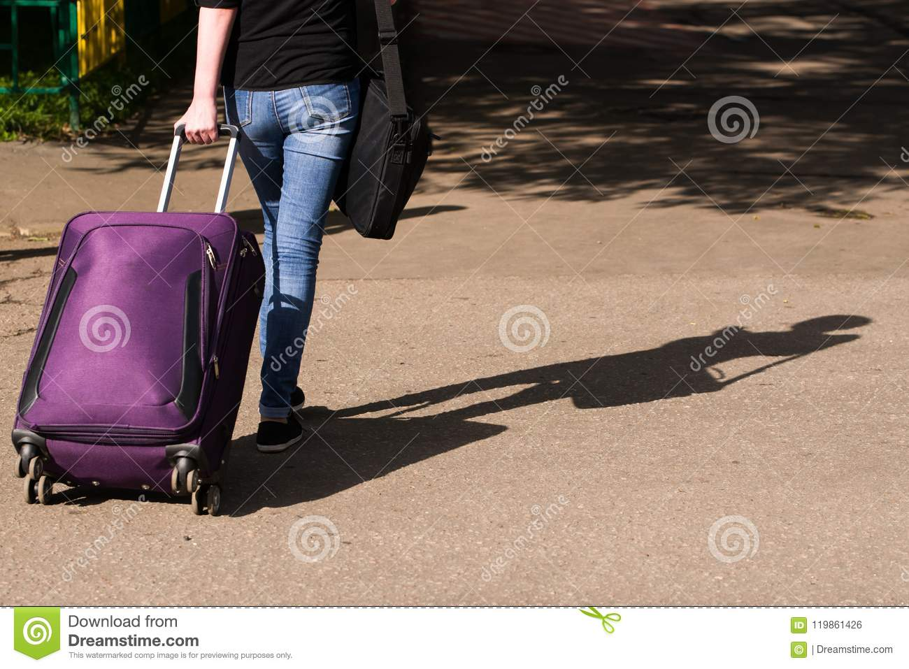Girl in jeans is on the road with a suitcase