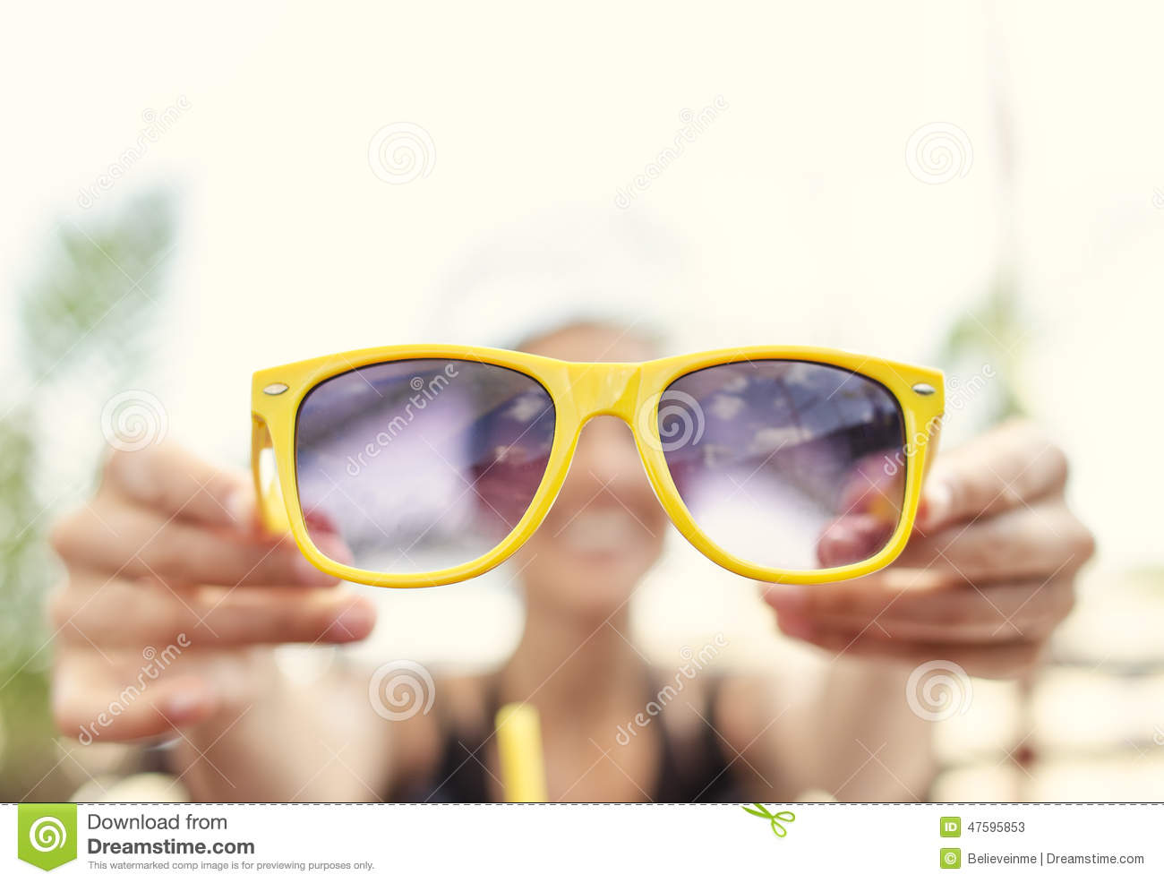 Have of blond teen holding sunglasses just, has