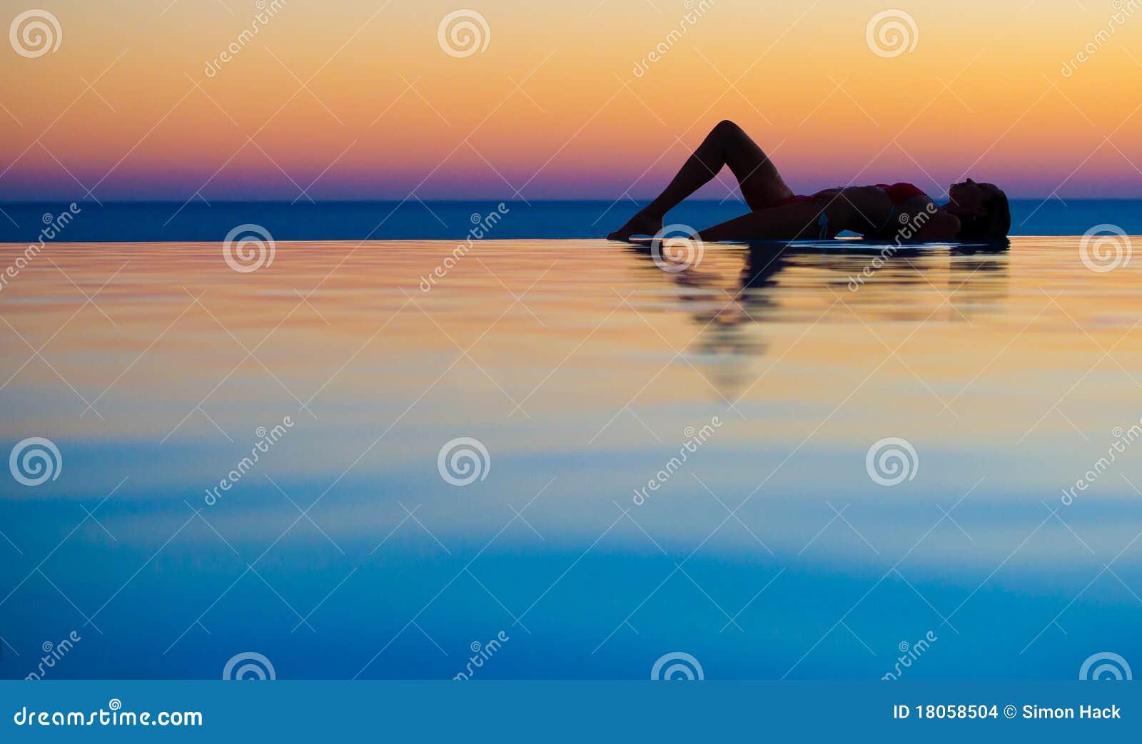 Girl in Sunset infinity pool
