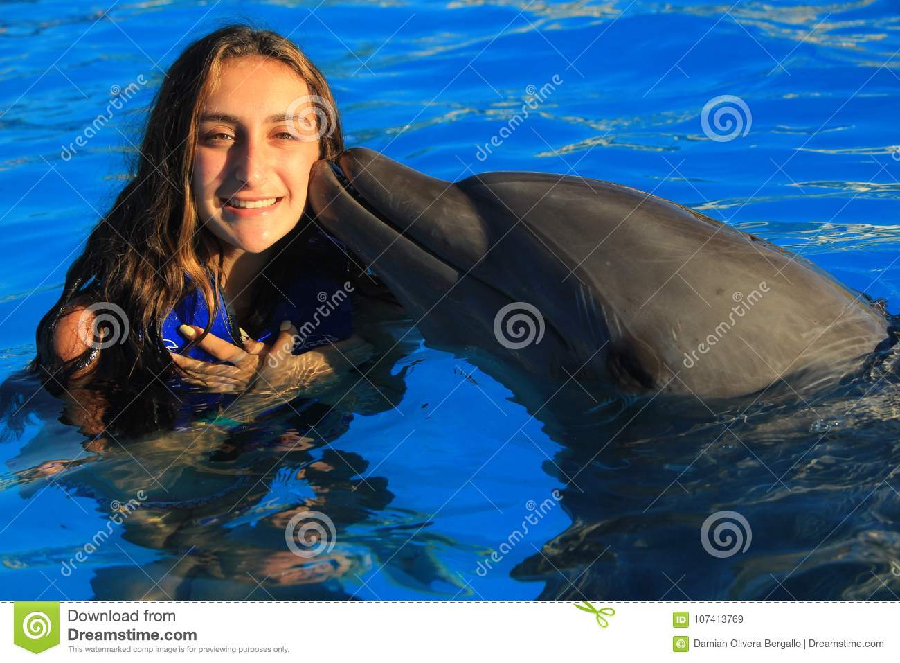 Beautiful girl kissing a gorgeous dolphin flipper smiling face happy kid swim bottle nose dolphins