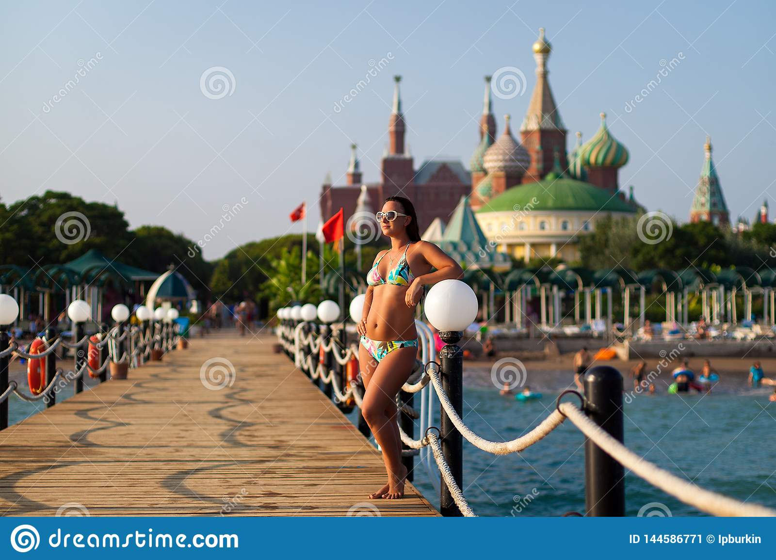 Girl in a swimsuit on the pier on the background of the hotel. girl posing on the wooden pier on the beach, against the backdrop
