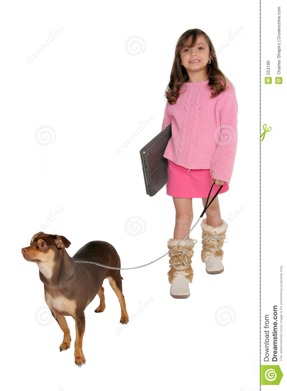 Girl take s dog for a walk carrying her laptop