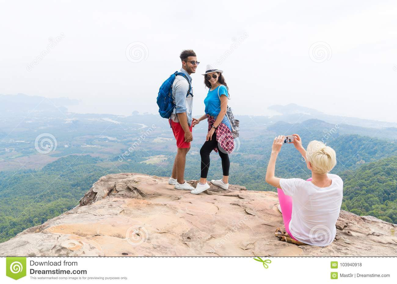 Girl Taking Photo Of Couple With Backpacks Posing Over Mountain Landscape On Cell Smart Phone, Trekking Young Man And