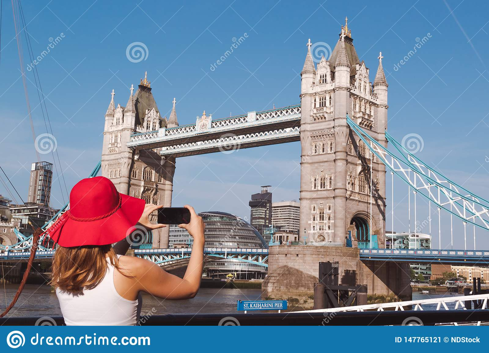 Young woman with red hat taking a photo of the Tower bridge in London